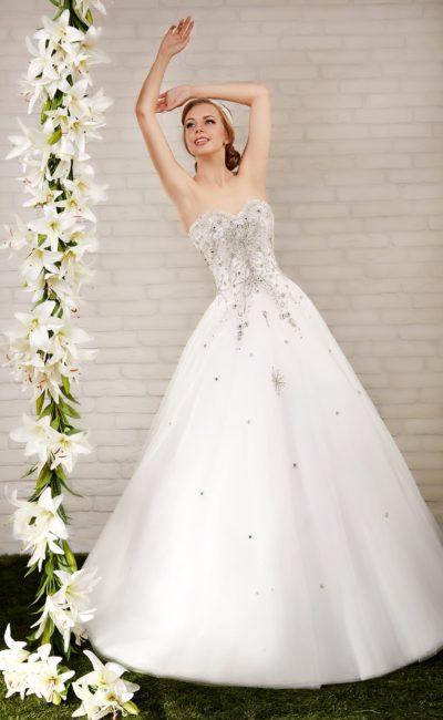 Пышное свадебное платье с корсетом, покрытым вышивкой серебристым бисером.