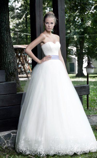 Открытое свадебное платье пышного силуэта с кружевным декором юбки и цветным поясом.