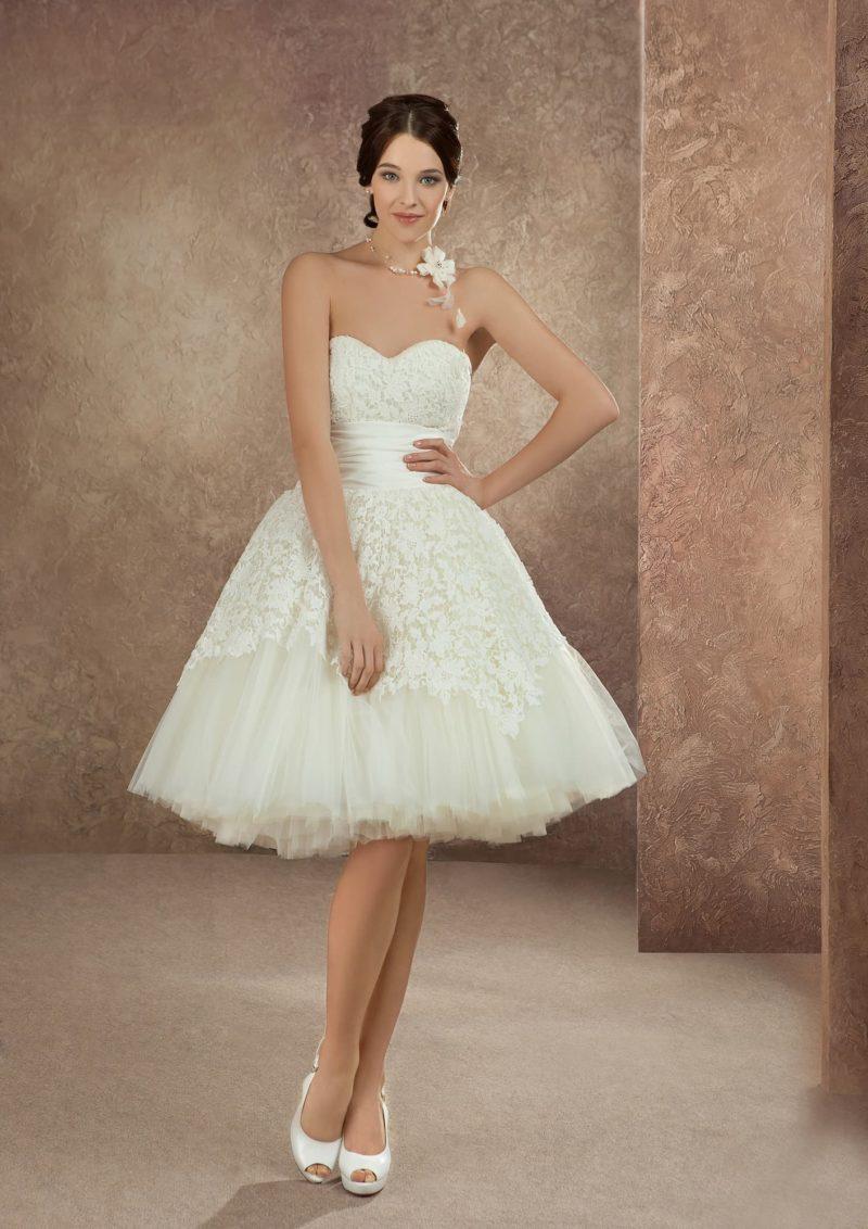 Короткое свадебное платье с пышной кружевной юбкой и открытым лифом в форме сердца.
