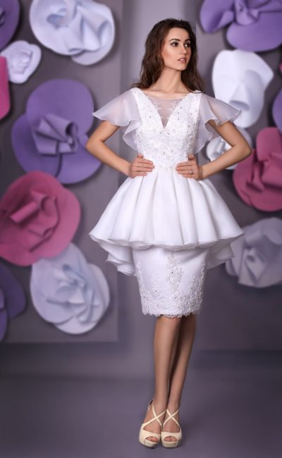 Короткое свадебное платье с пышной баской и объемными полупрозрачными рукавами.