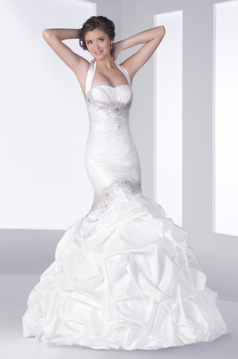 Свадебное платье с силуэтом «рыбка» из атласной ткани, украшенное волнами ткани по подолу.