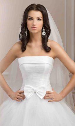 Романтичное свадебное платье пышного силуэта с крупным атласным бантом на линии талии.