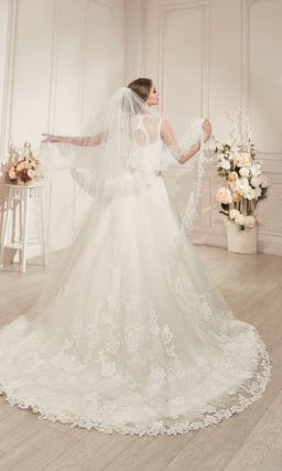 Свадебное платье «принцесса» с округлым вырезом, серебристым поясом и длинным шлейфом.