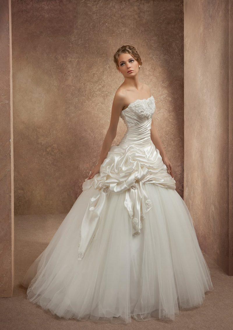 Пышное свадебное платье с атласным корсетом, украшенным бутонами и драпировками.
