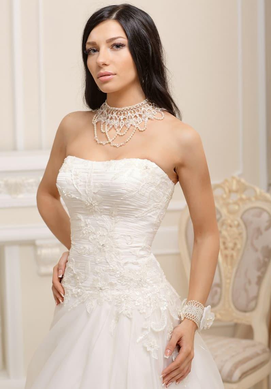 Свадебное платье силуэта «принцесса» с кружевной отделкой на открытом лифе.