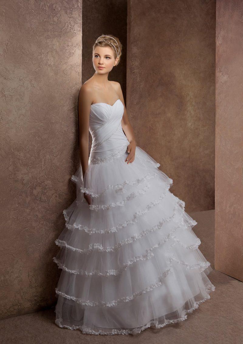 Свадебное платье с соблазнительным вырезом и пышной юбкой, декорированной оборками.