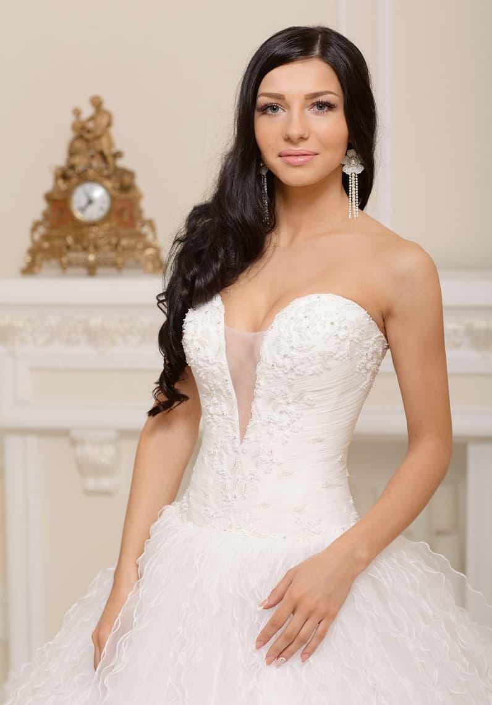 Пышное свадебное платье с бисерной вышивкой лифа и сложной отделкой юбки.
