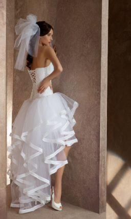 Свадебное платье с открытым лифом прямого кроя и короткой юбкой, дополненной сзади шлейфом.