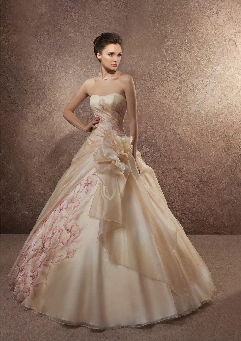 Пышное свадебное платье кремового цвета украшено оборками и цветочным рисунком по подолу.