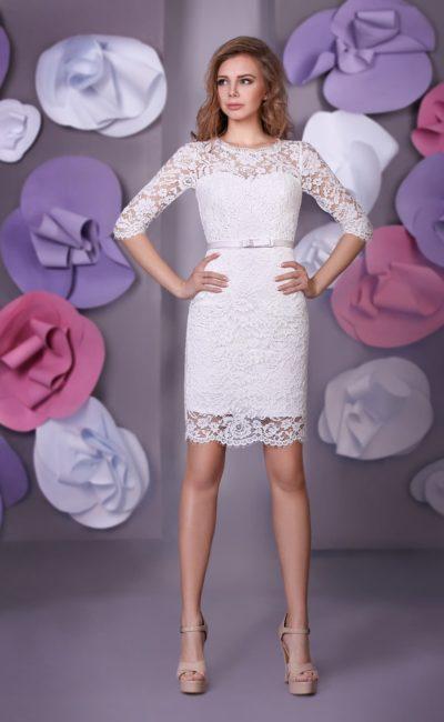 Короткое свадебное платье с прямым силуэтом и отделкой из кружева, создающей рукава до локтя.