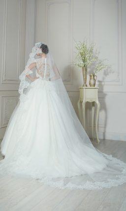 Пышное свадебное платье с глянцевым полупрозрачным верхом юбки и кружевной баской.