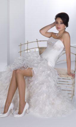 Короткое свадебное платье с открытым корсетом, украшенным драпировками, и оборками на юбке.