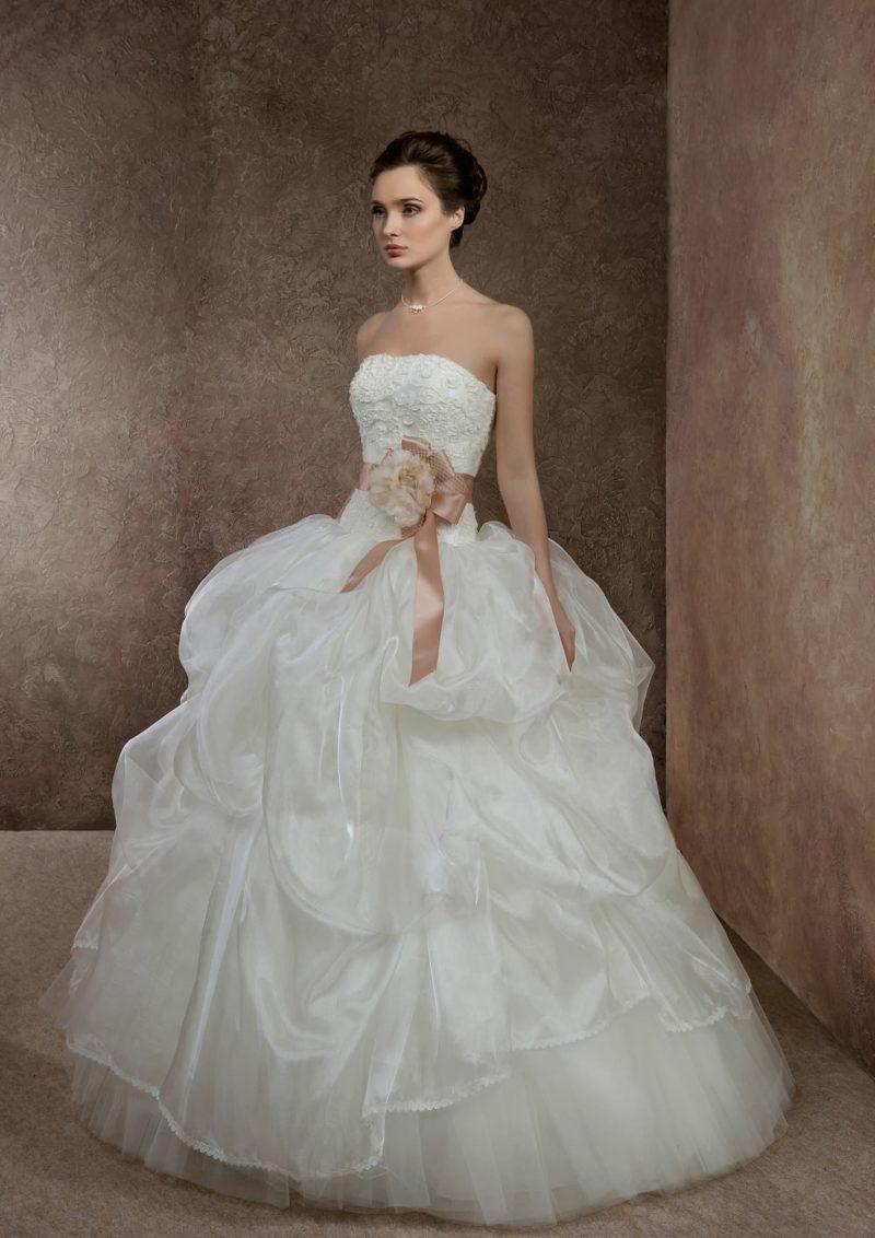 Свадебное платье с кружевным корсетом, атласным розовым поясом и пышной многослойной юбкой.