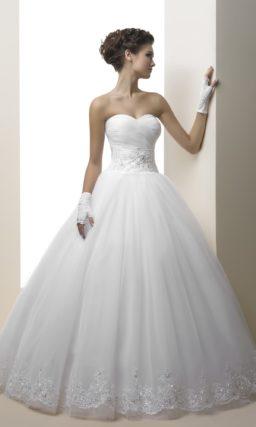 Изящное свадебное платье с классическим лифом и пышной юбкой, украшенной кружевом.