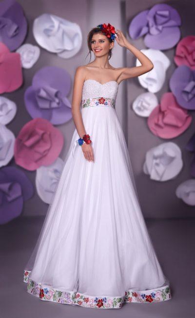 Открытое свадебное платье в ампирном стиле с отделкой цветной вышивкой по талии и подолу.