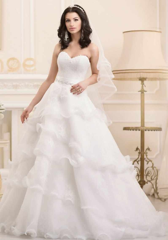 Изящное свадебное платье А-силуэта с полупрозрачными оборками на юбке.