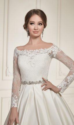Атласное свадебное платье пышного силуэта с фигурным округлым вырезом и длинными рукавами.