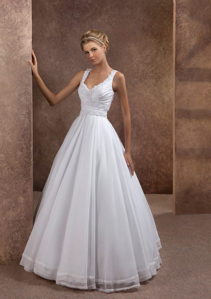 Пышное свадебное платье с V-образным декольте, обрамленным бретелями.