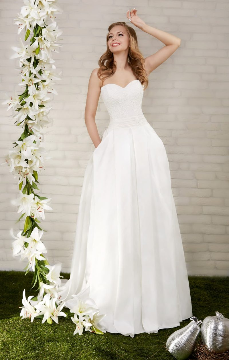 Открытое свадебное платье с женственным вырезом и пышной юбкой из атласной ткани.