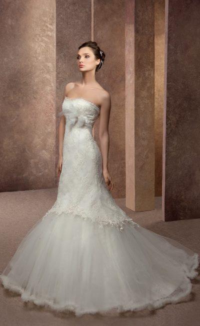 Открытое свадебное платье с подчеркнуто пышной юбкой силуэта «рыбка» и ажурной отделкой.