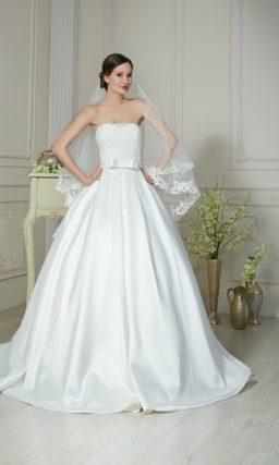 Пышное свадебное платье с атласной юбкой и поясом, украшенным крупным бантом.