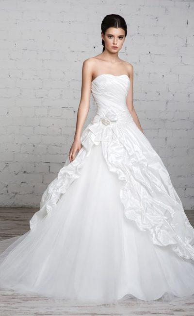 Торжественное свадебное платье из фактурной атласной ткани, спускающейся складками по пышной юбке.