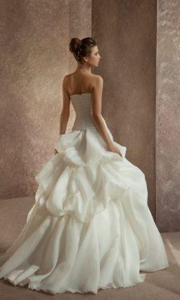 Пышное свадебное платье со шлейфом и элегантным корсетом, украшенным вышивкой.