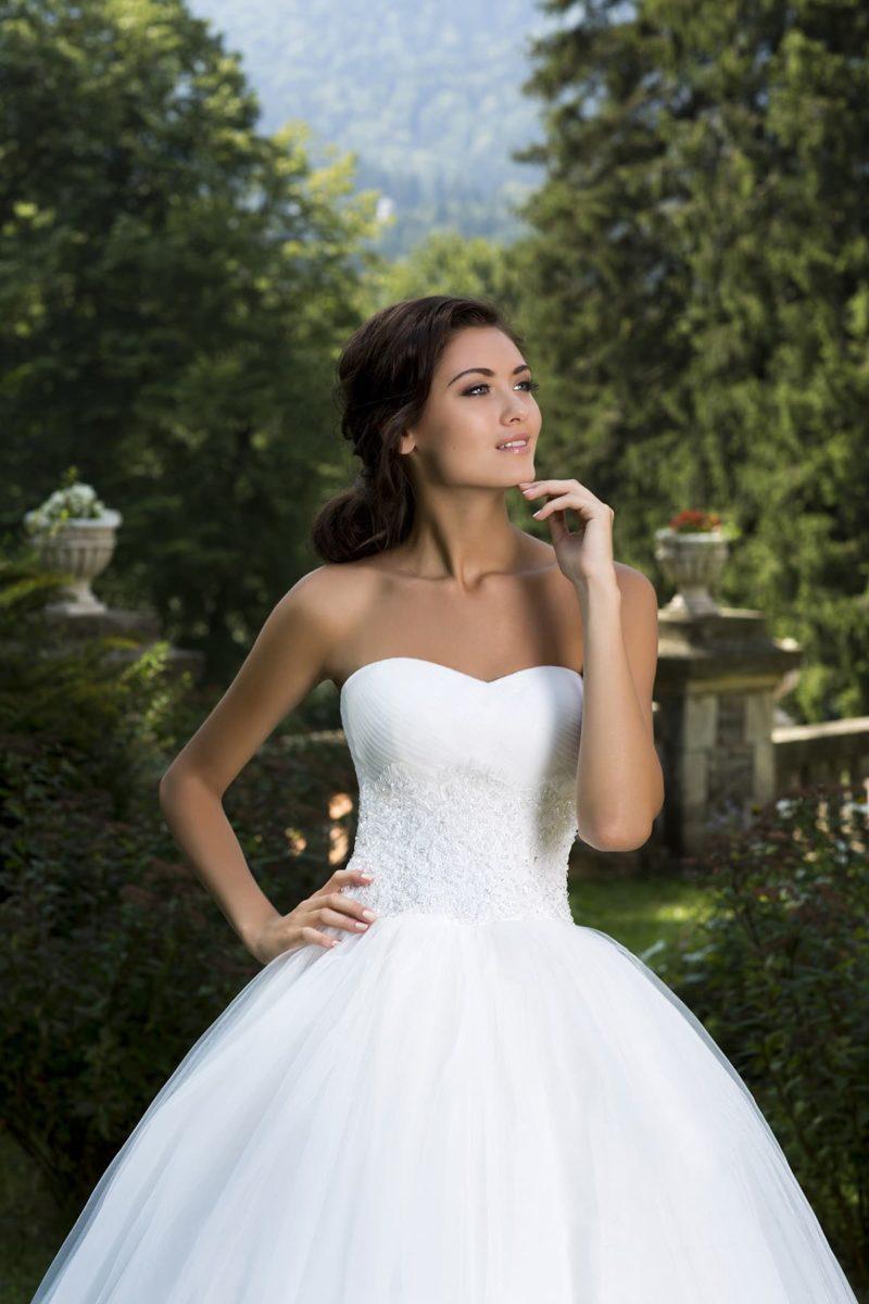 Торжественное свадебное платье с классическим корсетом и пышной юбкой из тонкой ткани.