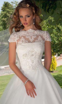 Пышное свадебное платье с ажурным болеро, дополняющим открытый лиф.