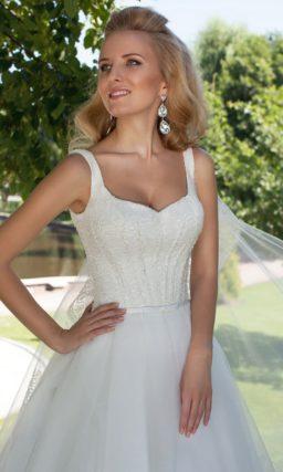 Лаконичное свадебное платье с украшенным бисером верхом.