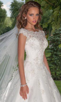 Свадебное платье с фигурным декольте, коротким рукавом и юбкой А-силуэта с шлейфом.