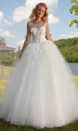 Пышное свадебное платье с закрытым верхом, оформленным тонкой тканью с вышивкой.