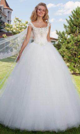 Изящное свадебное платье с подчеркнуто пышной юбкой и ажурными бретелями.