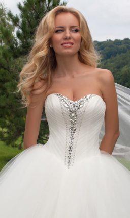 Пышное свадебное платье с драпировками и сверкающими стразами на корсете.