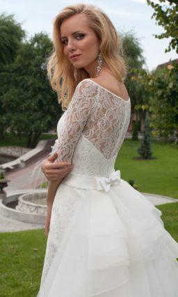 Прямое свадебное платье с округлым вырезом и пышным многоярусным шлейфом сзади.