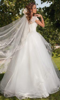 Пышное свадебное платье с короткими рукавами и многослойной прозрачной баской.