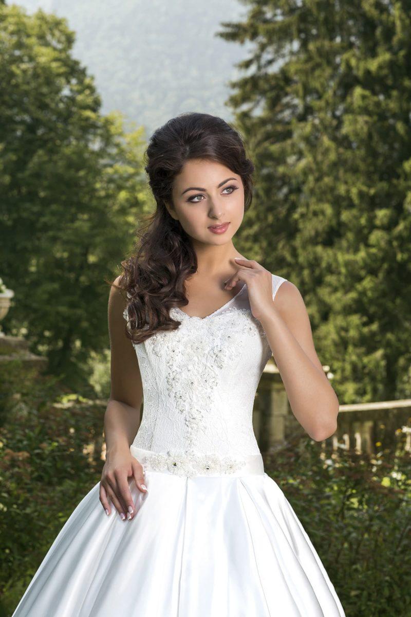 Пышное свадебное платье с V-образным декольте, обрамленным широкими бретелями.