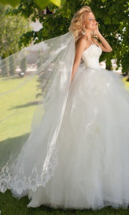 Восхитительное свадебное платье с пышной юбкой с оборками и открытым корсетом.