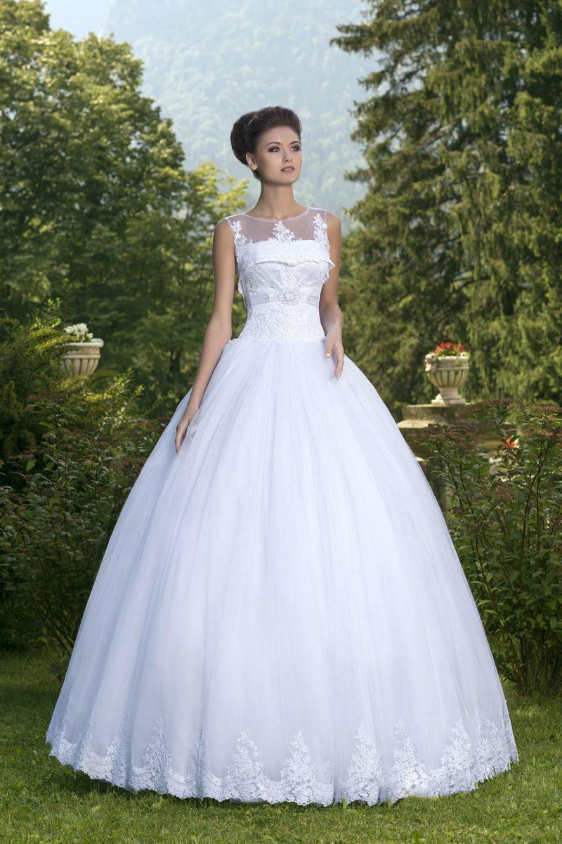 Пышное свадебное платье с полупрозрачной кружевной накидкой над лифом.