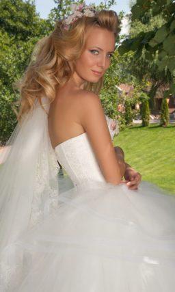 Открытое свадебное платье с пышной юбкой с роскошными оборками и вышивкой на лифе.