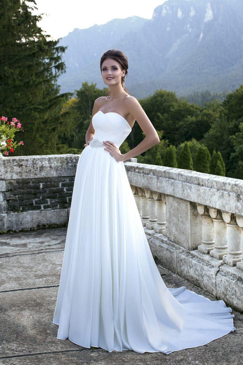 Прямое свадебное платье с открытым лифом в форме сердца и сверкающей вышивкой на талии.
