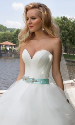 Пышное свадебное платье с глубоким чувственным декольте и цветным поясом из атласа.