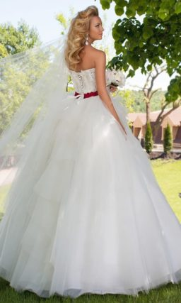 Пышное свадебное платье с многоярусной юбкой и алым атласным поясом на талии.