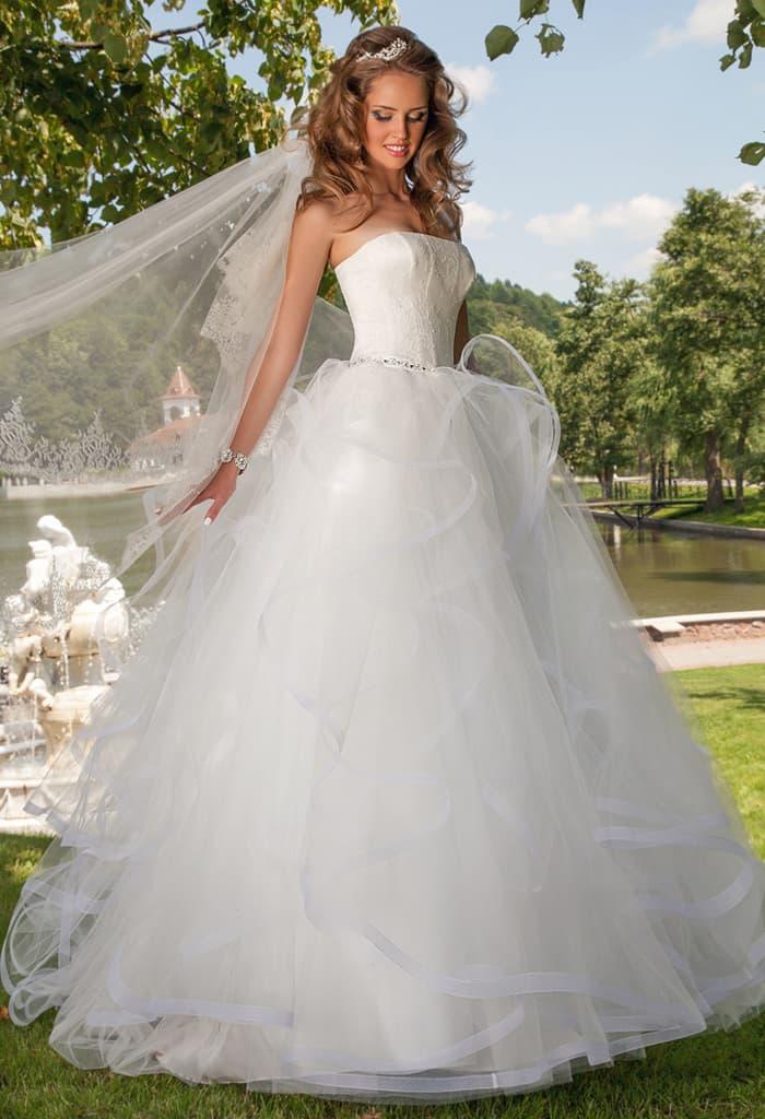 Открытое свадебное платье с декольте прямого кроя и многослойной юбкой с пышными оборками.