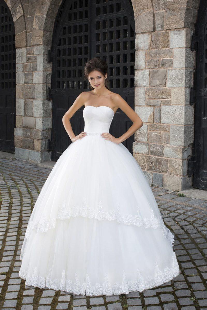 Свадебное платье с лаконичным открытым корсетом и многослойной юбкой с кружевом.