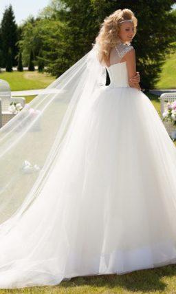Стильное свадебное платье пышного силуэта с вставкой над лифом, покрытой стразами.