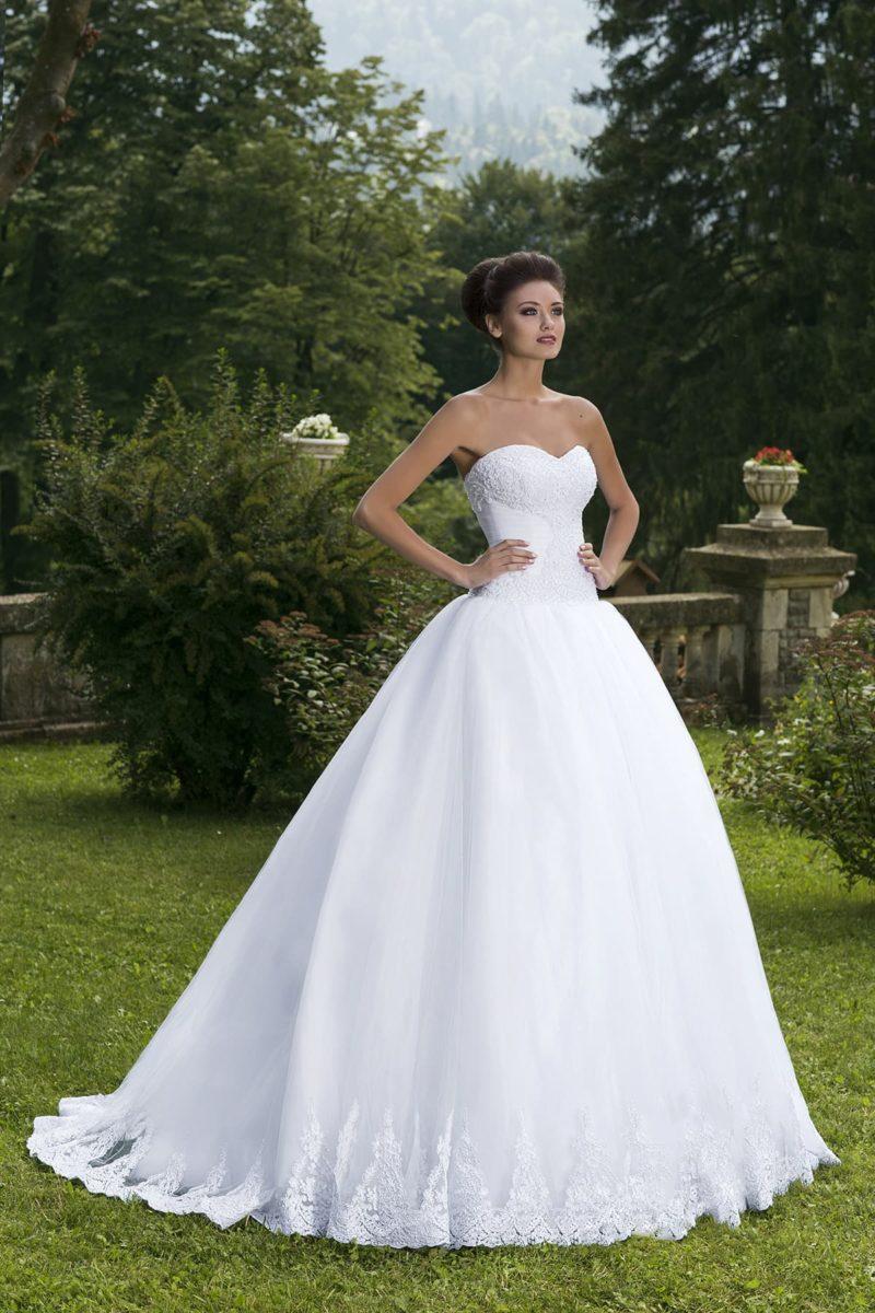 Открытое свадебное платье с невероятно пышной юбкой, по подолу со шлейфом украшенной кружевом.