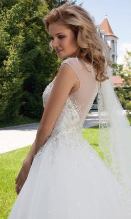 Пышное свадебное платье с многослойной юбкой и закрытым верхом, украшенным кружевом.