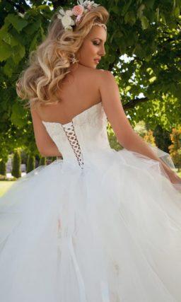 Шикарное свадебное платье пышного силуэта с открытым лифом и фактурным декором подола.