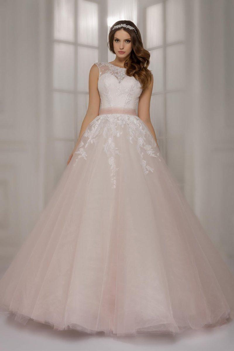 Свадебное платье с пышной юбкой кремового оттенка и полупрозрачным цветным поясом на талии.